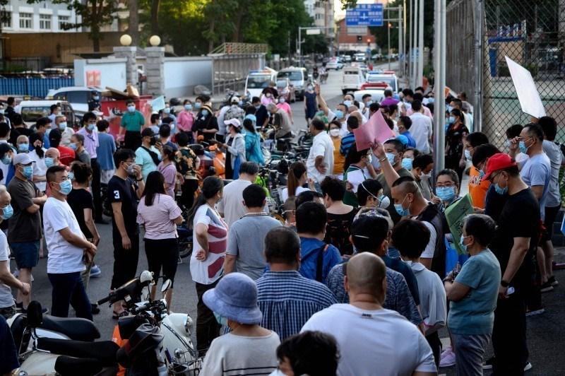北京自11日以来已累计106人确诊病例,官方15日宣布,北京全市社区防控工作进入「战时状态」,并展开「敲门行动」大排查;16日晚间,北京市政府举行记者会,宣布北京市突发公共卫生事件应急响应级别由三级调至二级,并相应调整防控策略。 图为曾至「新发地批发市场」的北京市民排队接受病毒筛检。 (法新社资料照)